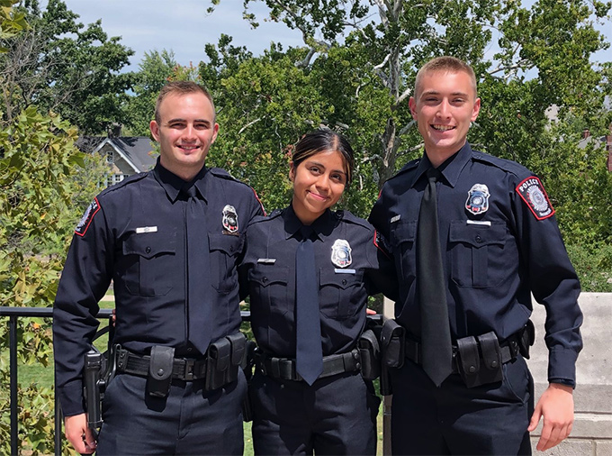 Chase Simpson, Ingrid Ortega, and Reece Thompson in uniform with trees in background