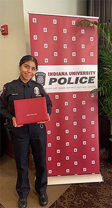 Ingrid Ortega in uniform holding her diploma in ballroom in front of vertical Indiana University Police banner